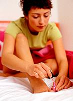 Young Woman Sitting on Bed Painting Her Toenails