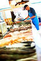 Mature worker unpacking fresh fish