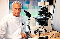 Portrait of confident male researcher working in laboratory with a microscope