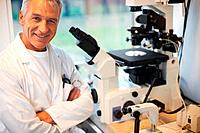 Portrait of smiling mature male scientist in laboratory with a microscope