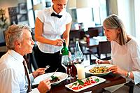 Mature caucasian couple dining in restaurant with a waitress serving wine