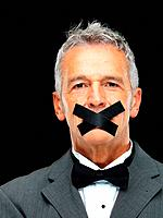 Portrait of mature business man with duct tape on his mouth over black background