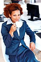Portrait of happy African American business woman having cup of coffee while sitting at her desk
