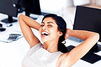 Female executive relaxing with her hands behind her head at work