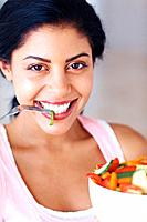 Closeup portrait of beautiful young woman eating vegetable salad
