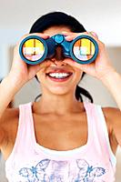 Closeup of cute young woman smiling while looking through binoculars