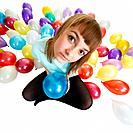 Young woman sitting on floor among balloons