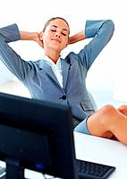 Beautiful young business woman resting with feet on desk