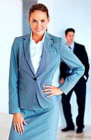Portrait of successful young business woman with male colleague in background