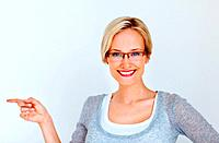 Portrait of pretty young business woman pointing sideways while presenting