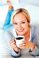 Portrait of smiling beautiful woman enjoying cup of coffee while relaxing on bed