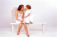 Mother and daughter dressed as angel, daughter making up mother