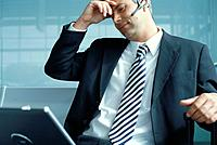 Businessman with headset using laptop