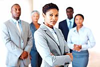 Portrait of confident middle aged female executive standing in front of colleagues