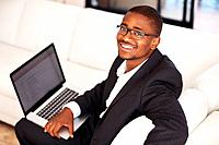Portrait of happy African American business man on sofa using laptop