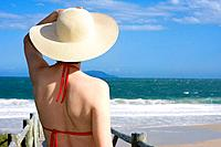 Woman with hat looking at the sea