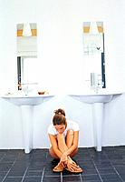 Young woman squatting down in bathroom