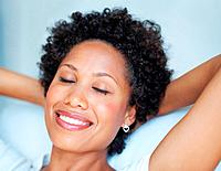 Closeup of beautiful African American woman relaxing with hands behind head