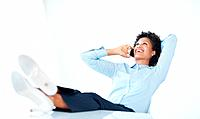 Relaxed African American business woman using cellphone with legs on desk