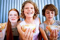 Three female teenagers with sandwiches