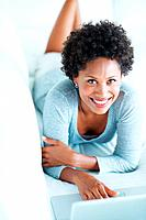 Portrait of smiling African American woman spending time at home using laptop
