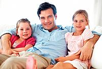 Portrait of handsome man with daughters sitting on sofa