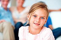 Closeup portrait of pretty little girl with family relaxing in background
