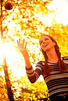 Young red_haired woman with plaits throwing an aple in the autumn