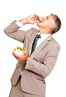 Portrait of mature business man enjoying fruit salad over white background