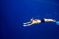 Underwater view of young female snorkeling in clear blue tropical sea water