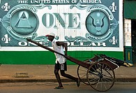 dark_skinned man pulling a rickshaw, painted Dollar bill on wall in background, Madagascar, Antsiranana, Diego Suarez