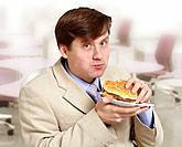 Young funny businessman eats a hamburger