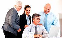 Group of four happy business people in meeting at office using laptop