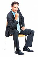 Portrait of a smart male business executive sitting on chair and thinking over white background
