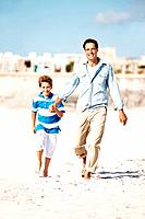 Portrait of father and son walking on the beach on a summer day