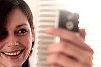 Woman taking photo of herself with mobile phone