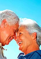 Closeup of senior couple with noses together against sky