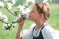 girl smelling at apple tree blossoms
