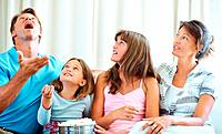 Family sitting together on a sofa with man tossing popcorn