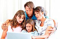 Family of four sitting together on sofa and using laptop