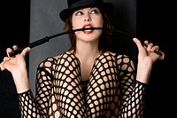 young woman lasciviously posing in a fishnet body with top head and whip