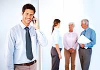 Smart young businessman speaking on mobile phone with colleagues in background
