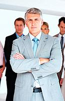 Portrait of confident mature businessman standing in front of his team