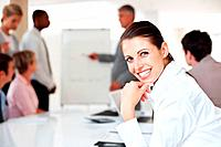 Portrait of a smiling young businesswoman smiling and her colleagues working on presentation at office