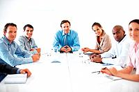 Portrait of business group sitting at table and smiling during meeting