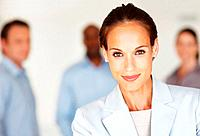 Closeup portrait of pretty business woman smiling with colleagues standing in background