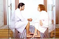 Young Man and Woman Sitting Face to Face, Wearing Bathrobes