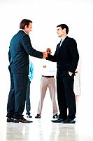 Full length of two business men shaking hands with colleagues in background