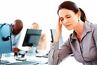 Business woman stressed at work with colleagues in background