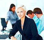 Beautiful businesswoman sitting by desk in office environment with colleagues in background